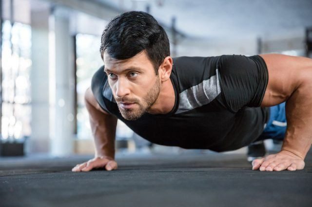 A man does a push up at a gym.