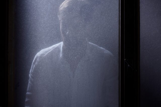 A man stands in front of a blurry window.