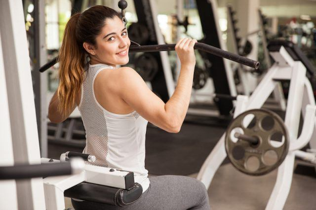 A woman does a shoulder workout at a gym and smiles.