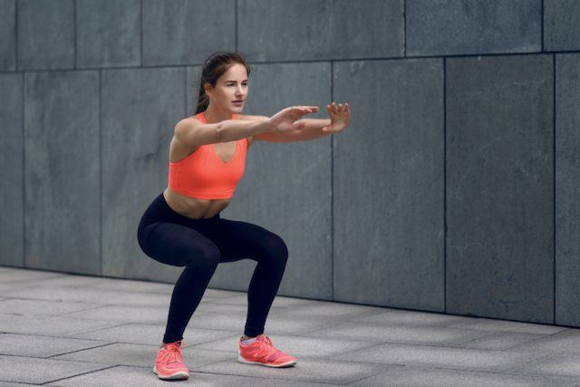 A woman does a squat while wearing an orange sports bra and black leggings.