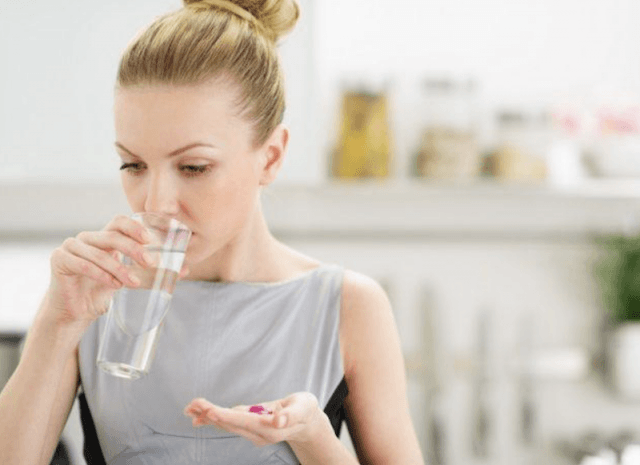 A woman drinks water while holding pill.