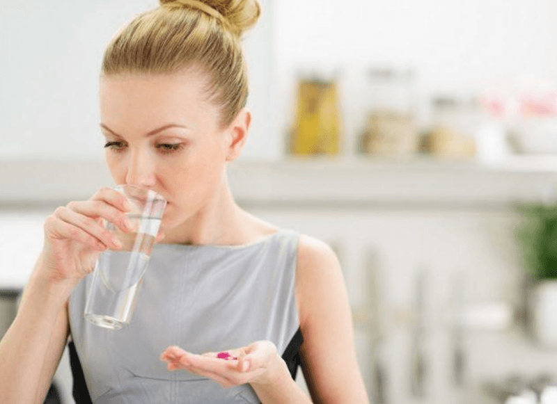 Woman swallowing a pill with water