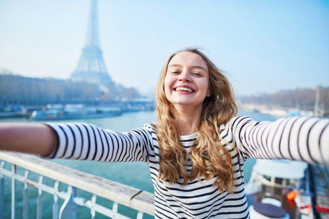 A woman takes a selfie in front of the Eiffel Tower.