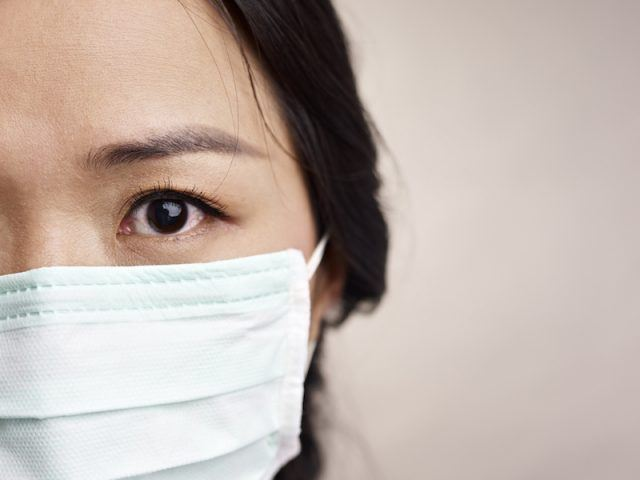 A woman wears a face mask and has a fearful look in her eye.