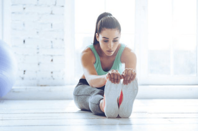 A woman stretches while sitting on the floor of a studio gym.