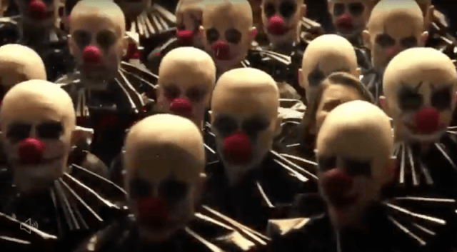 Clowns with red noses and white face paint standing in rows.