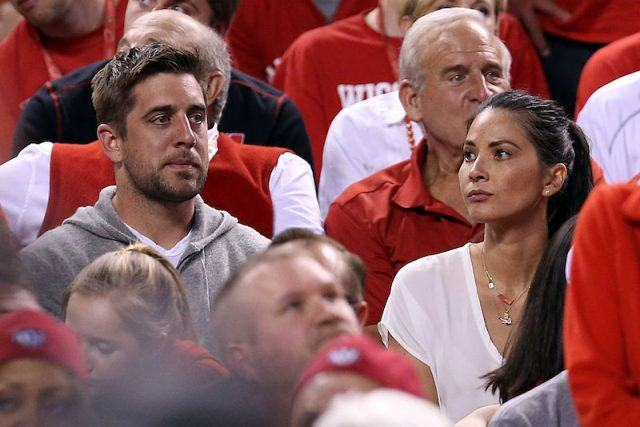 Aaron Rodgers and Olivia Munn look on during a football game in Indiana.