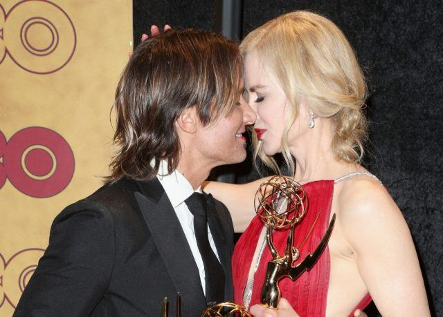 Singer Keith Urban and actress Nicole Kidman embrace while they stand on stage.