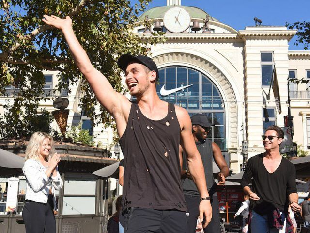 Alan Bersten waves at fans outside a Nike store.