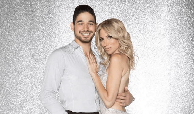 Alan Bersten and Debbie Gibson standing with each other in front of a glittery gray background.
