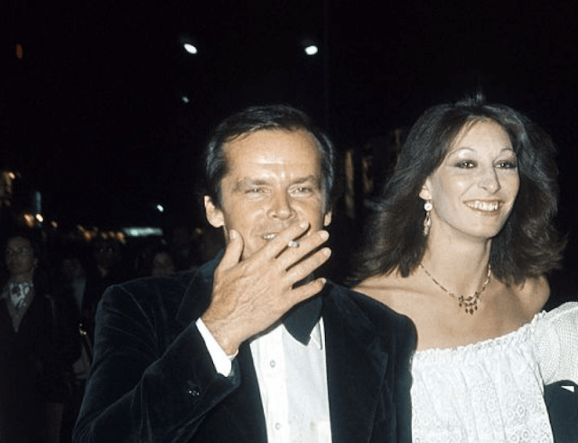 Jack smokes a cigarette and walks with Anjelica Huston at his side.