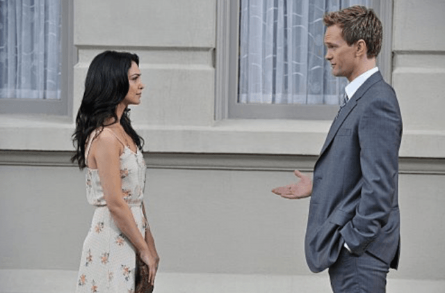 Barney and Nora talking in front of a building as they face each other.