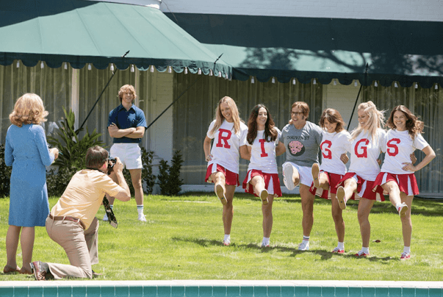 Steve Carell's Bobby Riggs poses for photos with cheerleaders on a lawn.