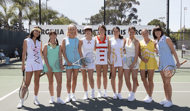 A line of female tennis players stand in a court