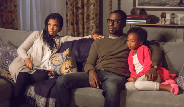 Beth, Randall, and their daughter sitting on a couch.