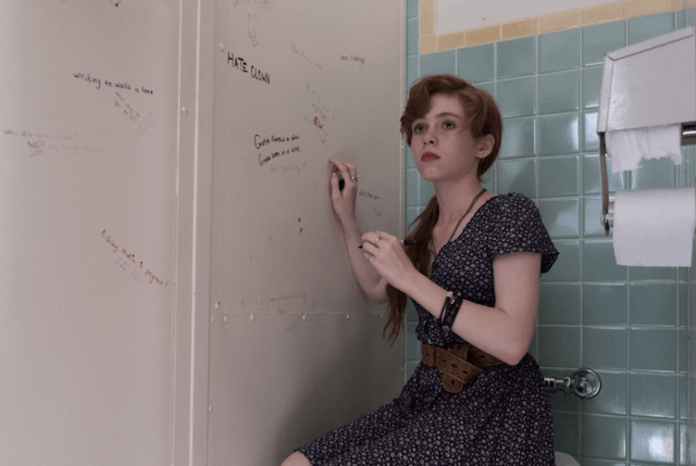 Beverly sits on a toilet seat while writing on a wall.