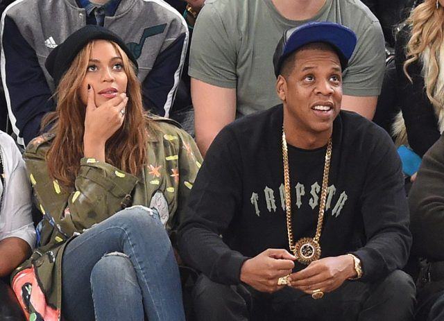 Beyoncé and Jay Z sit together at a basketball game.