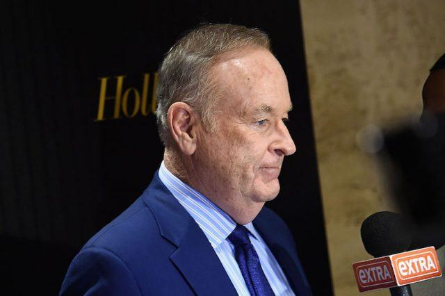 Bill O'Reilly stands in a blue suit in front of a mic.