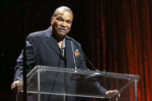 Billy Dee Williams stands at a glass podium during an awards show.
