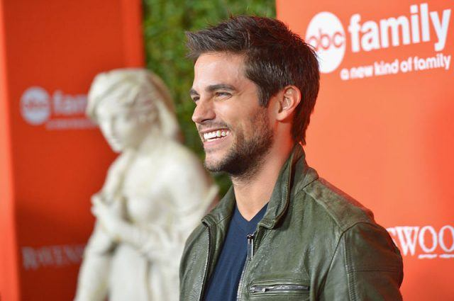 Brant Daugherty smiles and laughs at the red carpet of an ABC Family event.