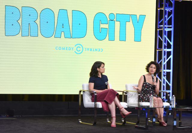 Abbi Jacobson and Ilana Glazer sit on white chairs while answering questions on a Viacom press panel.