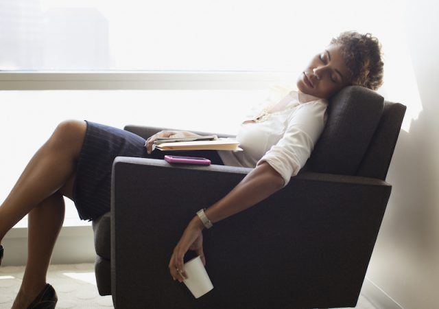 A woman falls asleep at work while taking a break on a chair.