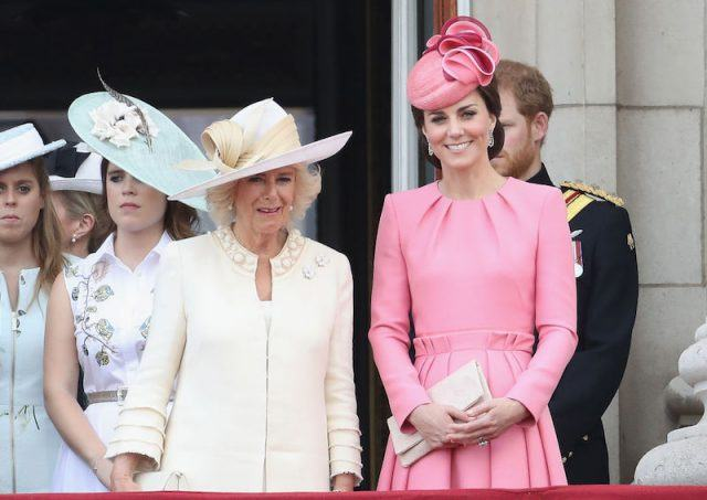 Camilla Parker Bowles and Kate Middleton standing next to each other while standing outdoors with their family.