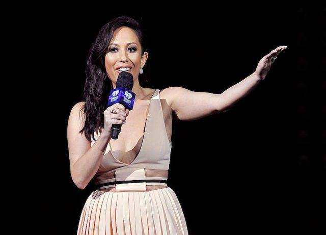 Cheryl Burke stands holding a microphone and holding up her left arm.
