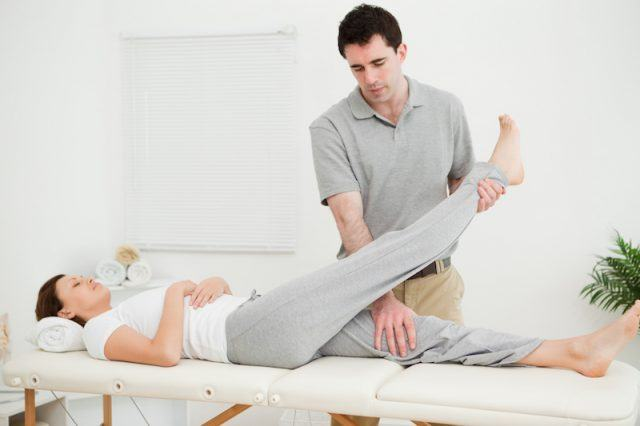 A chiropractor massages a patient's body.