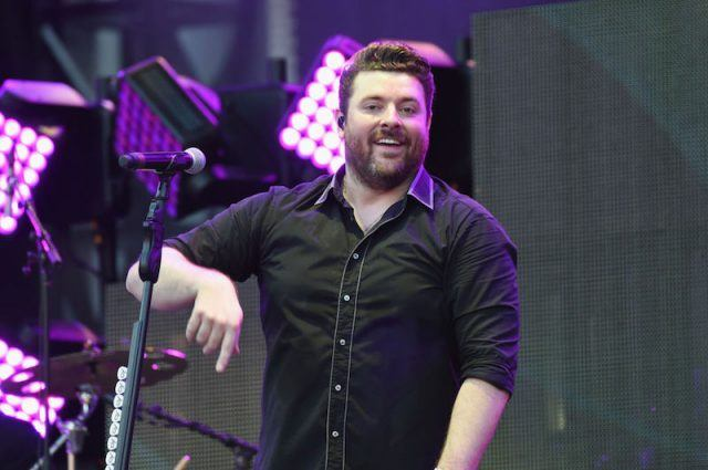 Chris Young standing on stage in front of a mic.