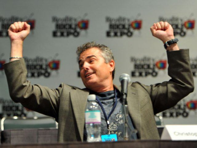 Christopher Knight raises both his arms while on a panel.