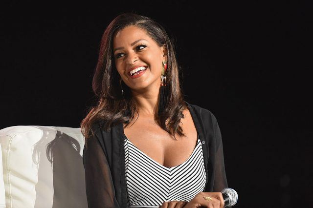 Claudia Jordan holding a microphone and sitting on a white couch.
