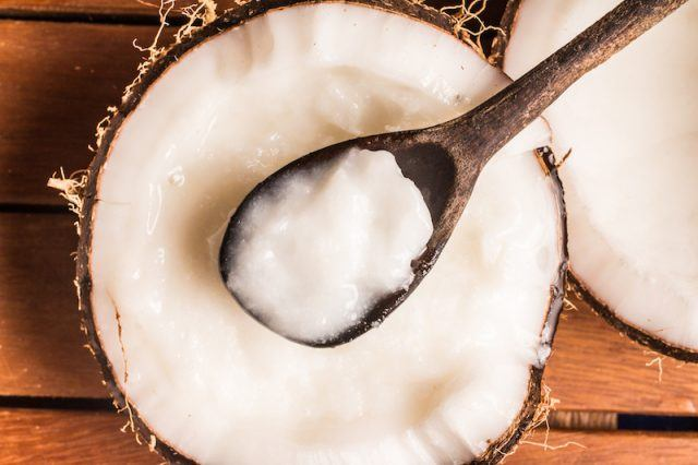 Coconut oil, half coconut and wooden spoon on table.