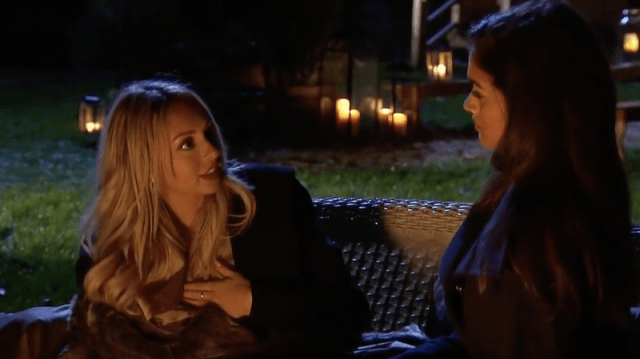 Corinne and Taylor have a discussion outdoors on a bench.