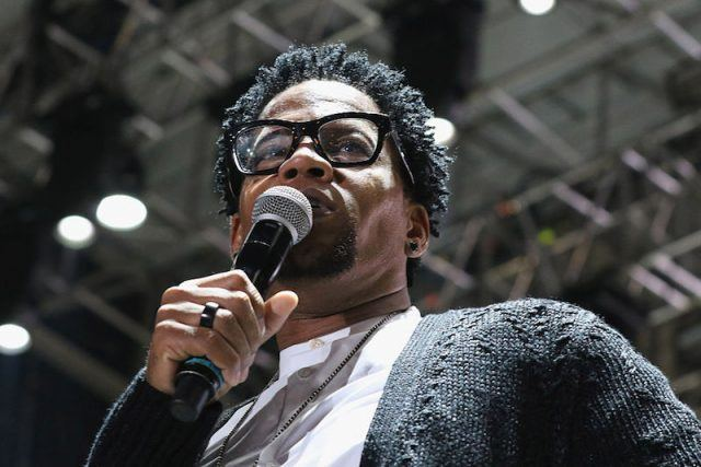 D.L. Hughley holds a microphone while speaking at a music event in Florida.