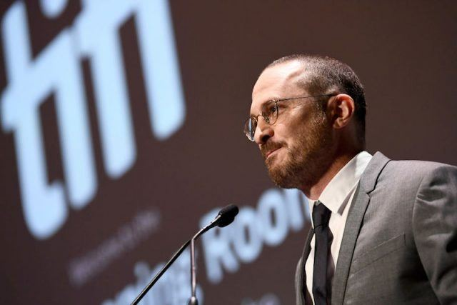 Darren Aronofsky speaks front on a microphone while wearing a gray suit.