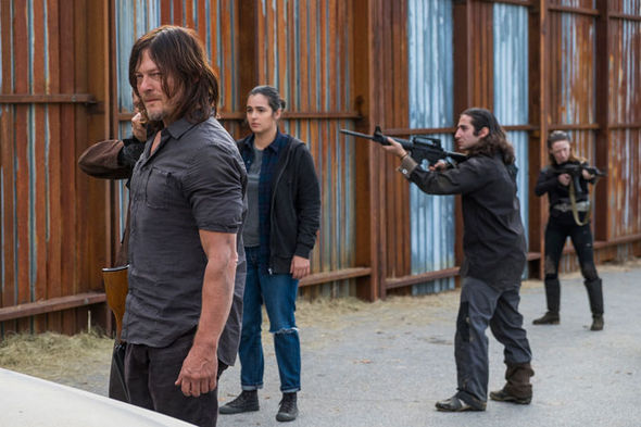 Daryl stands in front of a group of people holding guns