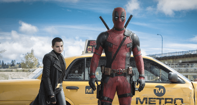 Deadpool stands in front of a yellow taxi.
