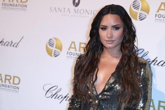 Singer Demi Lovato stands in a sequined outfit on a red carpet.