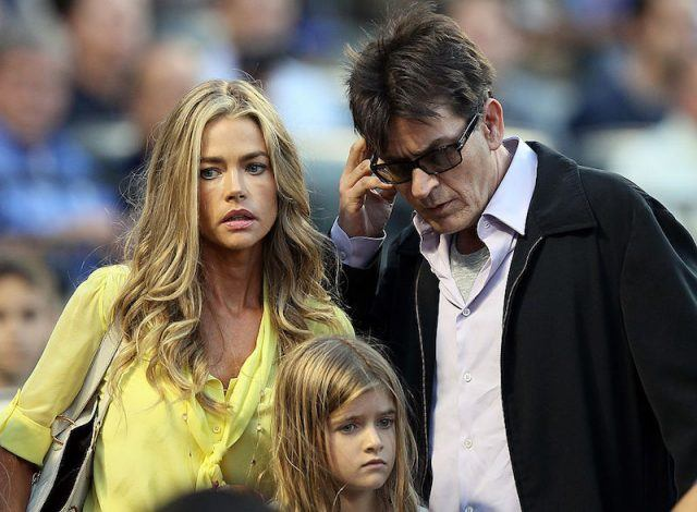 Denise Richard and Charlie Sheen walk with their daughter in a crowded stadium.