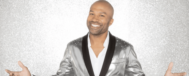 Derek Fisher smiles and holds up his hands while wearing a silver blazer.