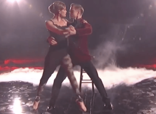 Derek Hough and Amy Purdy dancing together on stage in front of a prop stool.