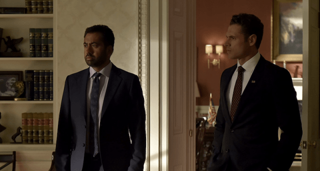 Kal Penn stands inside an office with a bookshelf with Aaron.