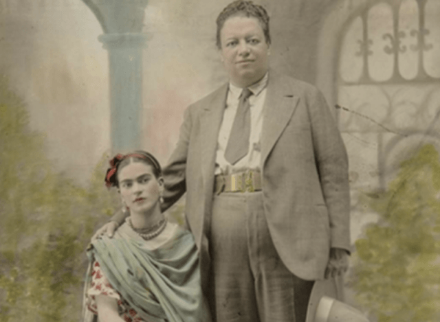 Frida and Diego stand together in front of a garden.