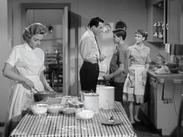 Donna Reed and her family standing in their kitchen, all doing various things.