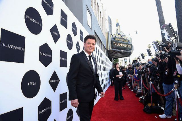 Donny Osmond poses in a tux on the red carpet.