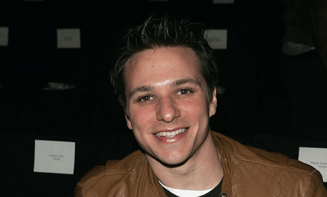 Drew Lachey smiles while sitting down in a tan jacket.