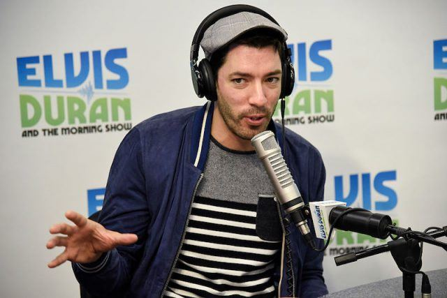 Drew Scott wears a headset and speaks into a mic while appearing on a radio talk show.