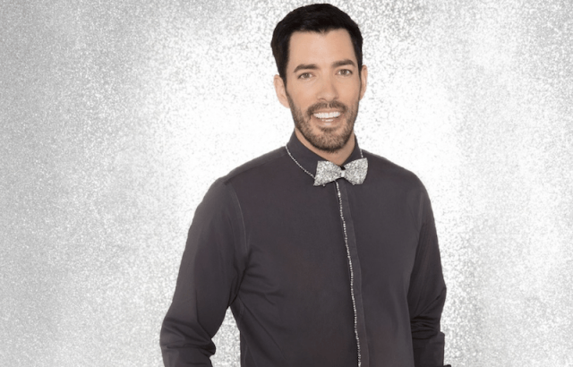 Drew Scott smiling and wearing a silver bowtie in front of a gray background.