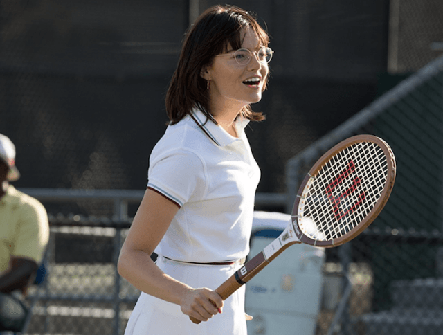 Emma Stone's Billie Jean King holds a tennis racquet while in a tennis court.